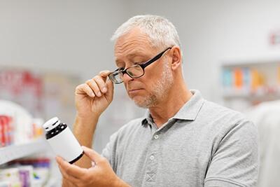 man reading prescription botttle